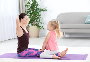 Sportive woman doing fitness exercises with daughter at home
