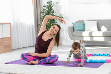 Woman doing fitness exercises together with son at home