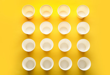 Paper cups on color background, top view. Picnic table setting