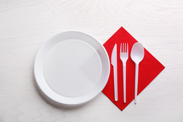 Composition with plastic dishware on wooden table, flat lay. Picnic table setting