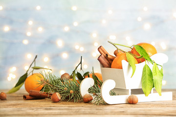 Christmas composition with toy sleigh and ripe tangerines on wooden table. Space for text