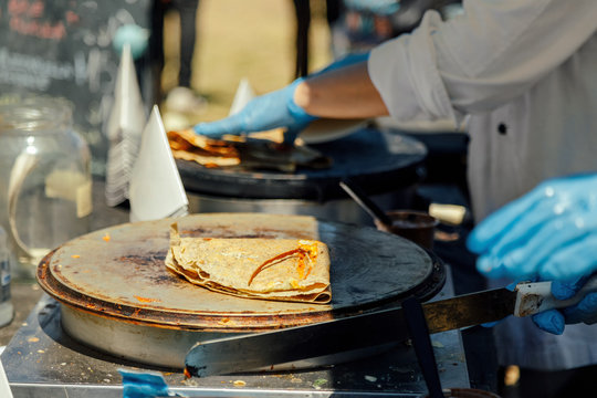 Crepe folded on a hot plate while another is cooked in the background