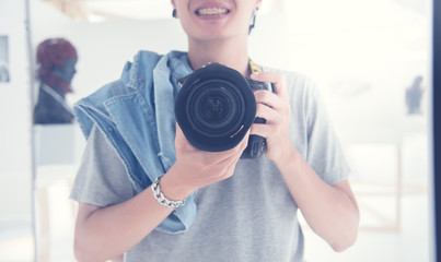 Happy professional photographer , Young photographer taking pictures with  digital DSLR camera.