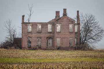 Large abandoned and derelict mansion on middle of field
