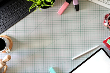 Graphic designer's workspace with a pencil tablet,  computer, color swatches and copy space on cutting board