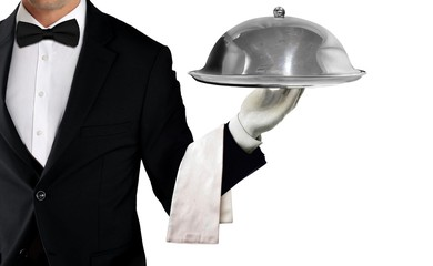 Waiter in tuxedo holding serving tray with metal cloche and napkin on white background