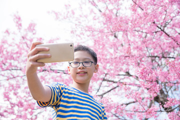 Young asian boy using smart phone taking photo himself in front of pink cherry tree