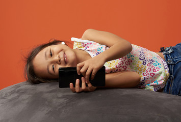 Asian kid smiling with phone