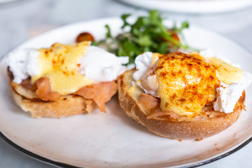 Eggs Benedict, English muffin topped with a poached egg, smoked salmon, and hollandaise sauce.