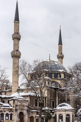 Eyup Sultan Mosque in winter in the snow. The mosque is situated in the Eyup district of Istanbul, outside the city walls near the Golden Horn.