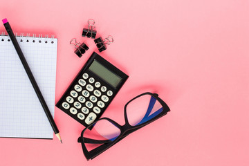Notepad,  calculator, pencil and glasses on  pink background. Top view, flat lay