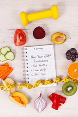 Fruits and vegetables, dumbbell and tape measure, new year resolutions of healthy lifestyles concept