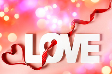 Word Love at pink background with bokeh lighting