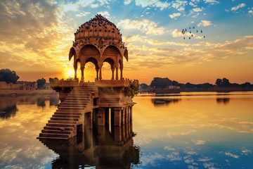 Ancient architecture ruins at Gadi Sagar (Gadisar) lake Jaipur Rajasthan at sunrise with vibrant moody sky.  Fototapete