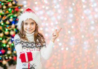 Smiling girl holding  gift box and pointing away. Empty space for text