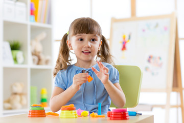 Cute kid playing with sculpting toy in daycare. Little girl with plasticine.