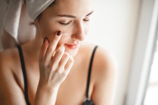 skin care. cute girl smears cheek face cream