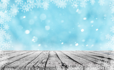 a wooden table and winter snow background with snowflakes