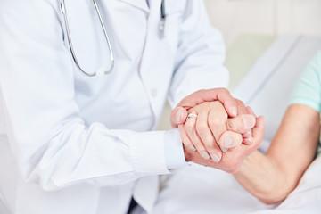 Arzt hält die Hand einer Patientin