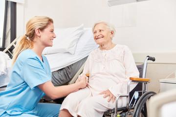 Altenpflegerin betreut Senior Frau im Rollstuhl