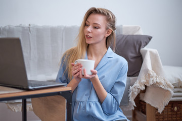 girl drinks coffee at home and works at a laptop or watching news