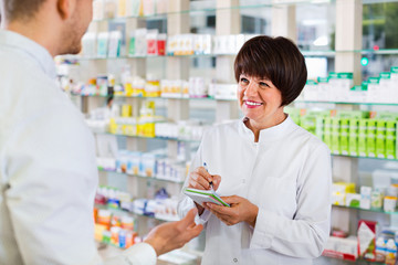 Smiling female pharmacist wearing uniform working