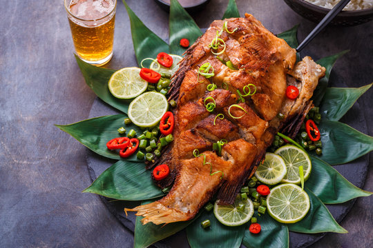 Deep fried whole fish with spicy sauce and coconut rice, thai cuisine.