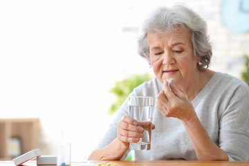 Elderly woman taking pill at home