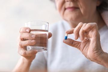 Elderly woman taking pill, closeup