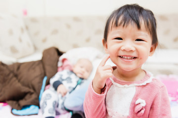 Closeup of happy little child playing over the bed in a relaxed morning with her little baby sister.