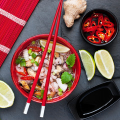 Asian soup with shrimp and vegetables. Top view on stone background