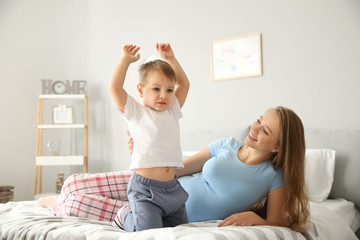 Young pregnant woman playing with her little son at home