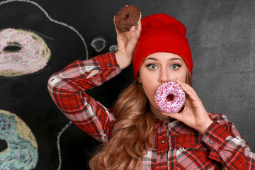 Funny young woman with tasty donuts on dark background