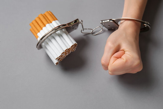 Woman handcuffed to cigarettes on grey background. Concept of addiction