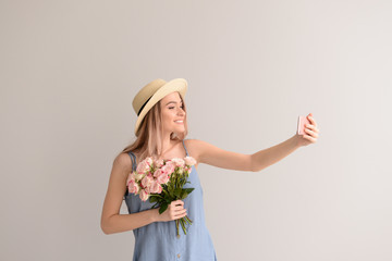 Beautiful young woman with bouquet of flowers taking selfie on grey background