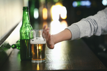 Young woman refusing to drink alcohol in bar