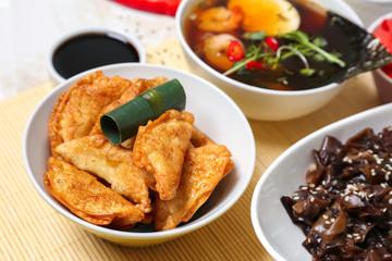 Tasty Chinese dumplings in bowl on table