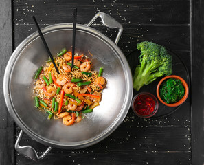 Chinese noodles with shrimps and vegetables in wok on wooden table