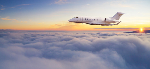 Luxury private jetliner flying above clouds.