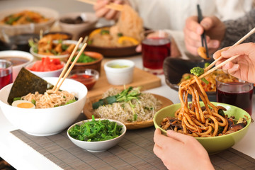 Woman with friends eating tasty Chinese food at table
