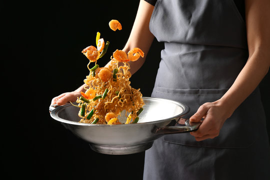 Woman cooking tasty Chinese noodles in wok on dark background