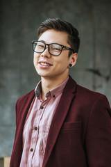 portrait of handsome young kazakh man in eyeglasses smiling at camera