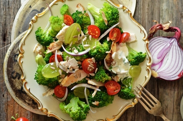 Salad with chicken, broccoli and cherry tomatoes on a rustic saucer on a wooden background