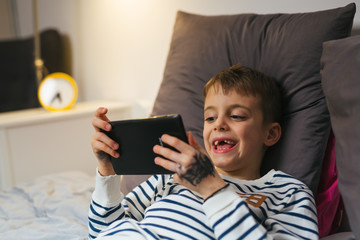 young boy laying bed and using tablet at home