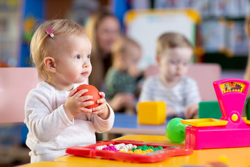 Cute little child playing with toys in nursery
