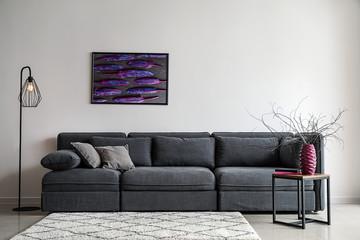Stylish interior of living room with comfortable grey sofa