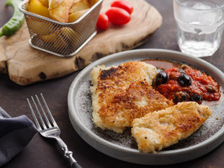 Fried fish with tomato-olive sauce and potatoes.