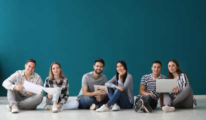 Team of young people sitting on floor in office Wall mural