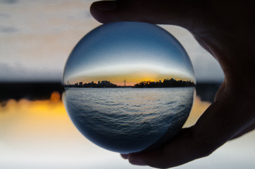 Silhouette of cityscape with dark ocean view photography  in clear crystal glass ball.