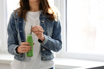 Woman with bottle of tasty smoothie indoors